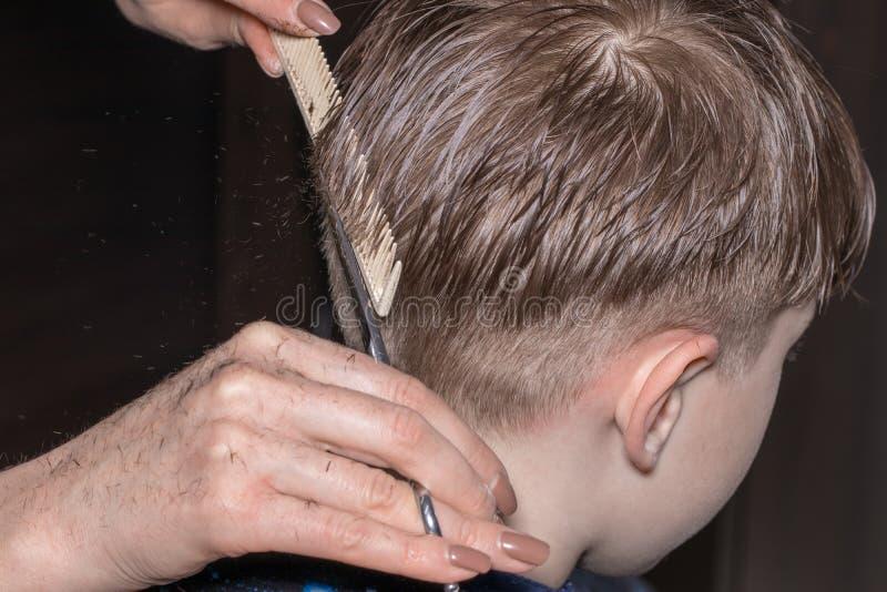 Vue de côté du petit garçon mignon obtenant la coupe de cheveux par le coiffeur à t photos libres de droits
