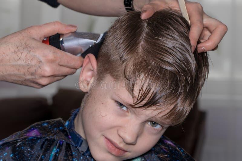 Vue de côté du petit garçon mignon obtenant la coupe de cheveux par le coiffeur à t photo libre de droits