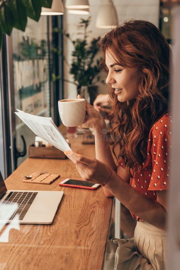 vue de côté de femme avec la tasse du journal de lecture de café à la table avec l'ordinateur portable photo stock