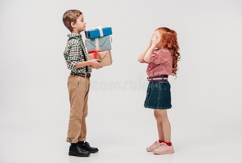 vue de côté de garçon présentant des cadeaux aux yeux se fermants mignons de petite fille image libre de droits