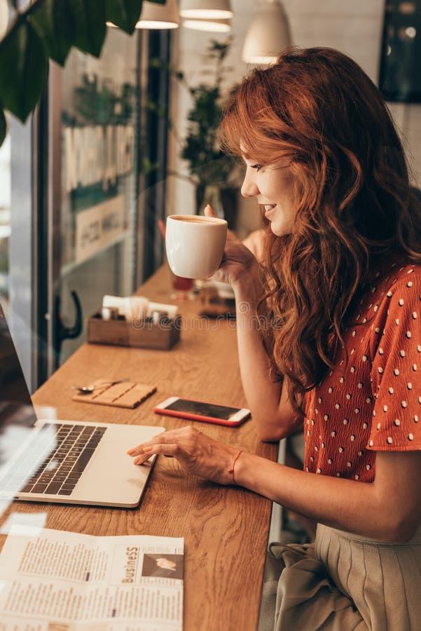 vue de côté de jeune blogger avec la tasse de café travaillant sur l'ordinateur portable photo stock