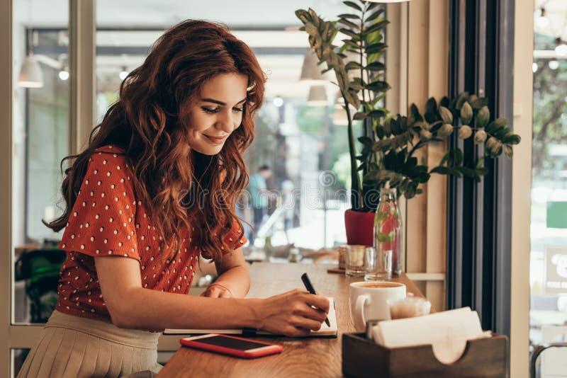 vue de côté de jeune blogger faisant des notes dans le carnet à la table avec la tasse de café photos stock