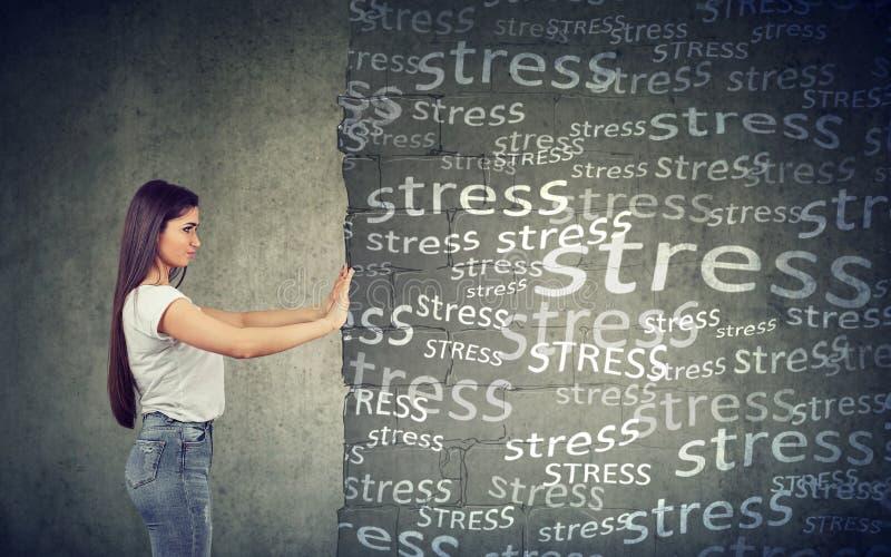 Vue de côté de jeune femme éloignant le mur de bloc avec l'effort photos stock