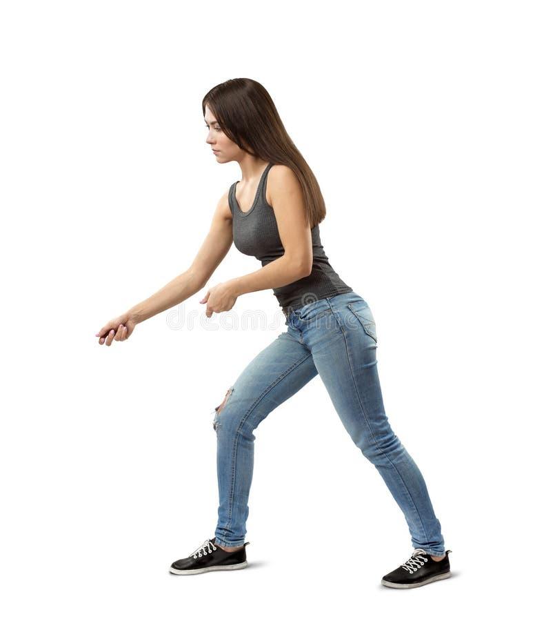 Vue de côté de jeune femme convenable dans le dessus gris et de blues-jean se pliant en avant légèrement et posant comme si tenan photo stock