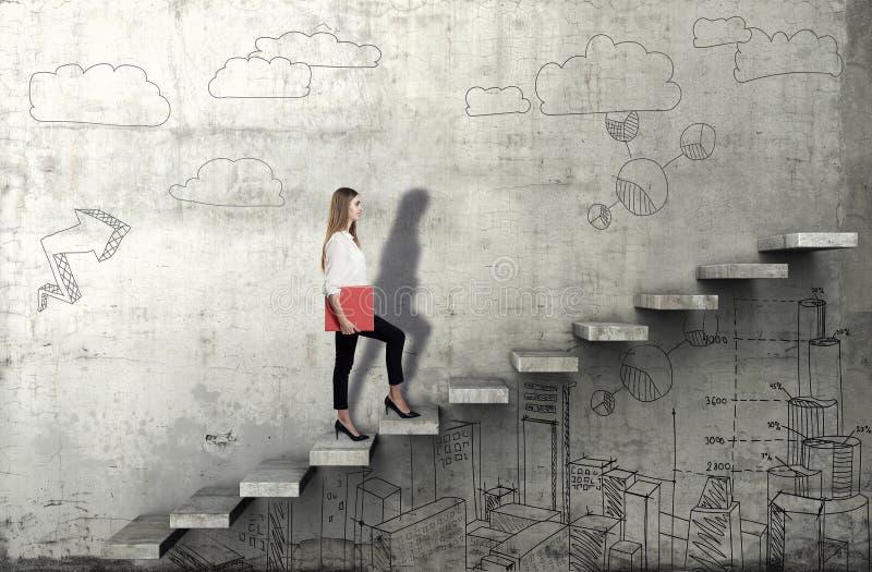 Vue de côté de jeune femme d'affaires montant les escaliers avec le croquis d'affaires sur le fond concret photo stock