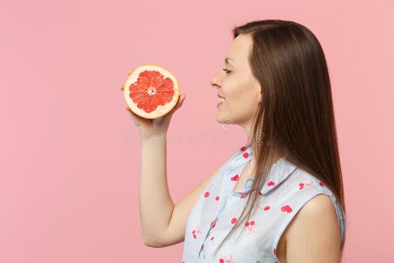 Vue de côté de jeune femme de sourire dans des vêtements d'été tenant la moitié disponible du pamplemousse mûr frais d'isolement  photographie stock libre de droits