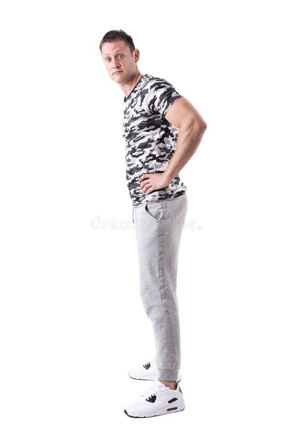 Vue de côté de jeune homme adulte expressif indifférent dans la chemise d'armée et l'habillement de sport regardant la caméra photos stock