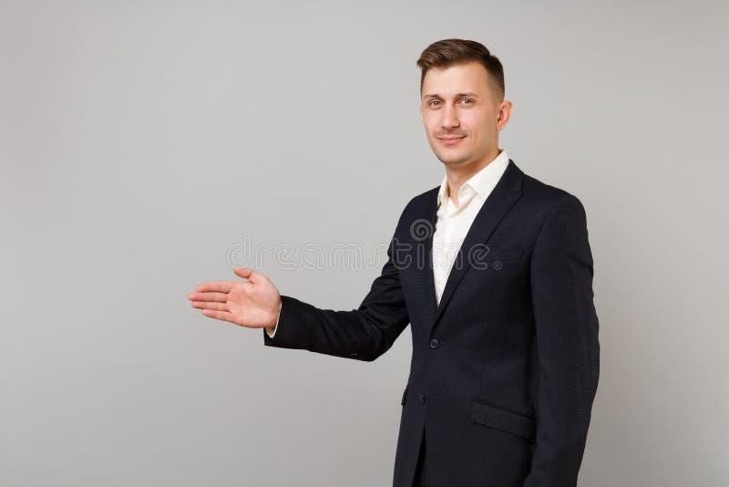Vue de côté de jeune homme beau d'affaires dans la position classique de costume avec la main tendue pour saluer d'isolement sur  photo libre de droits