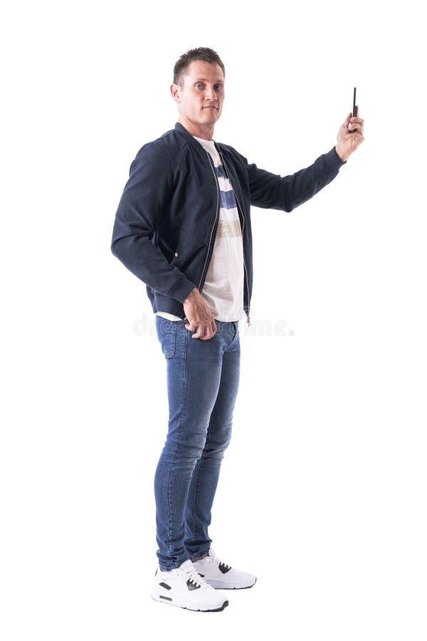 Vue de côté de jeune homme prenant des photos avec le téléphone portable et regardant l'appareil-photo images libres de droits
