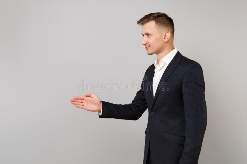 Vue de côté de jeune homme réussi d'affaires dans la position noire de costume avec la main tendue pour saluer d'isolement sur le photo libre de droits
