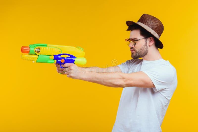 vue de côté de jeune homme tenant l'arme à feu d'eau et regardant loin photo libre de droits