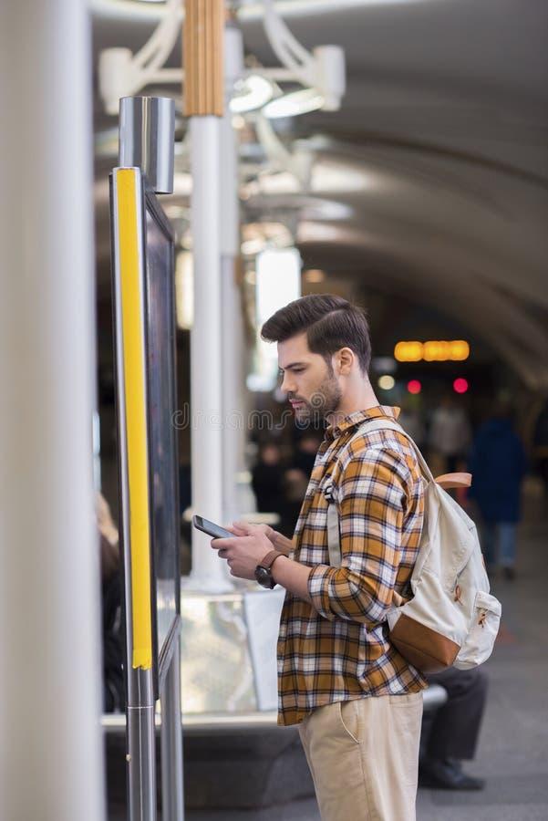 vue de côté de jeune touriste masculin avec le sac à dos et le smartphone regardant le conseil de l'information le souterrain photos libres de droits