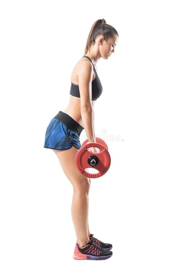 Vue de côté de l'athlète de femme d'ajustement faisant l'exercice de deadlift avec le barbell en mi position image libre de droits