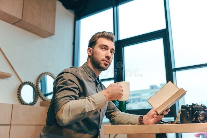 vue de côté de l'homme avec la tasse du café et du livre dans des mains se reposant à la table image stock