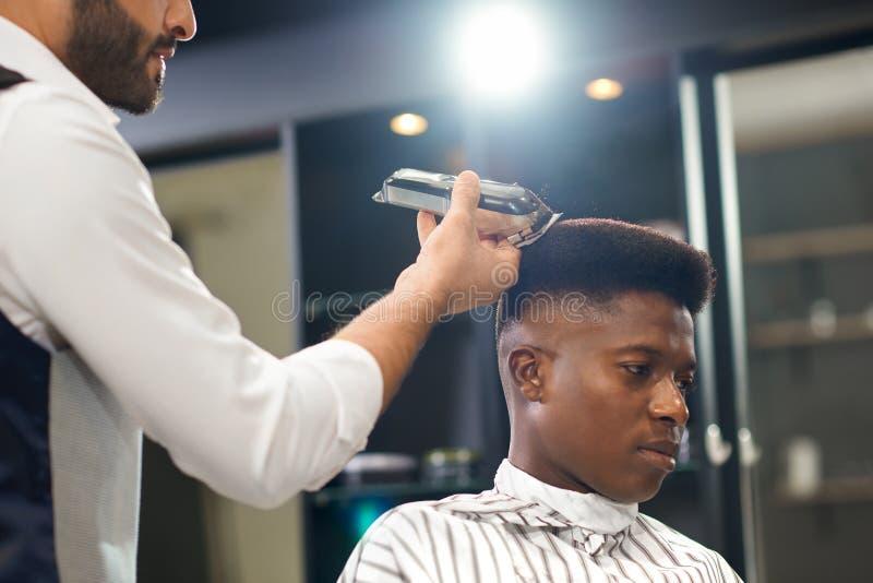 Vue de côté de l'homme obtenant la coupe de cheveux à la mode dans le salon de coiffure photos libres de droits