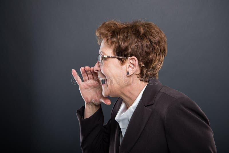 Vue de côté de la dame supérieure d'affaires faisant hurler le geste photo stock