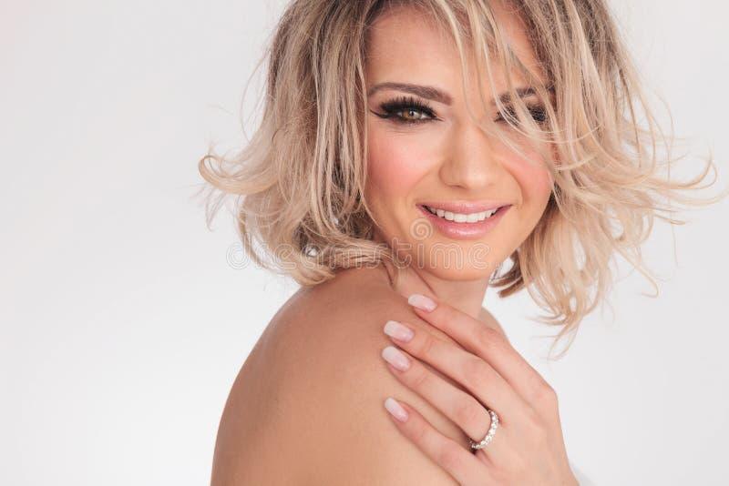 Vue de côté de la femme blonde de sourire touchant son épaule nue image stock