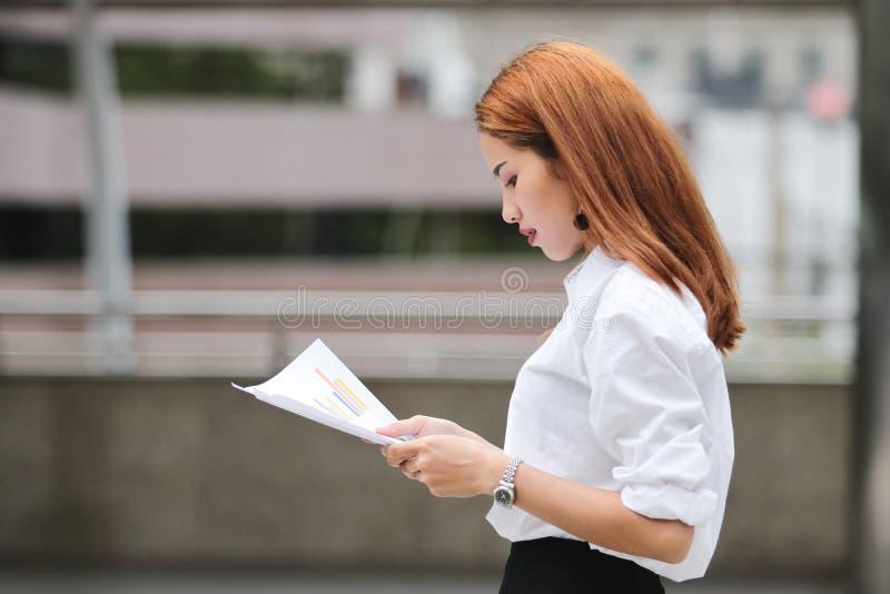 Vue de côté de la jeune femme asiatique sûre d'affaires analysant des diagrammes ou des écritures pendant la marche photo libre de droits