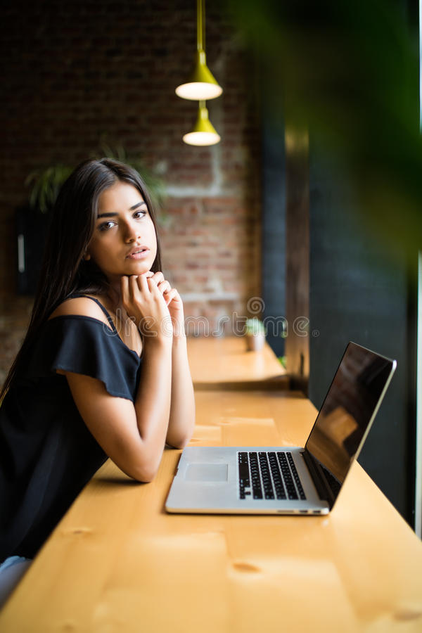 Vue de côté La jeune femme s'asseyant à la table en café et fait des notes dans le carnet En ligne apprenant Étudiant faisant le  image libre de droits