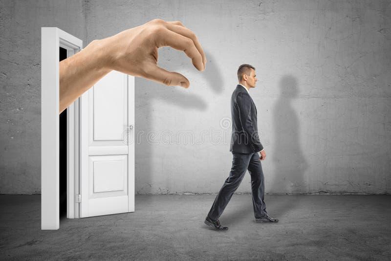 Vue de côté de la main du grand homme émergeant de l'obscurité sur la porte blanche et prêt à saisir peu d'homme d'affaires qui m illustration libre de droits