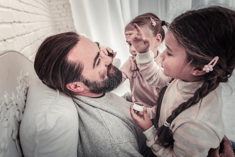 Vue de côté de la peinture de filles que leurs pères font face avec composent photos stock