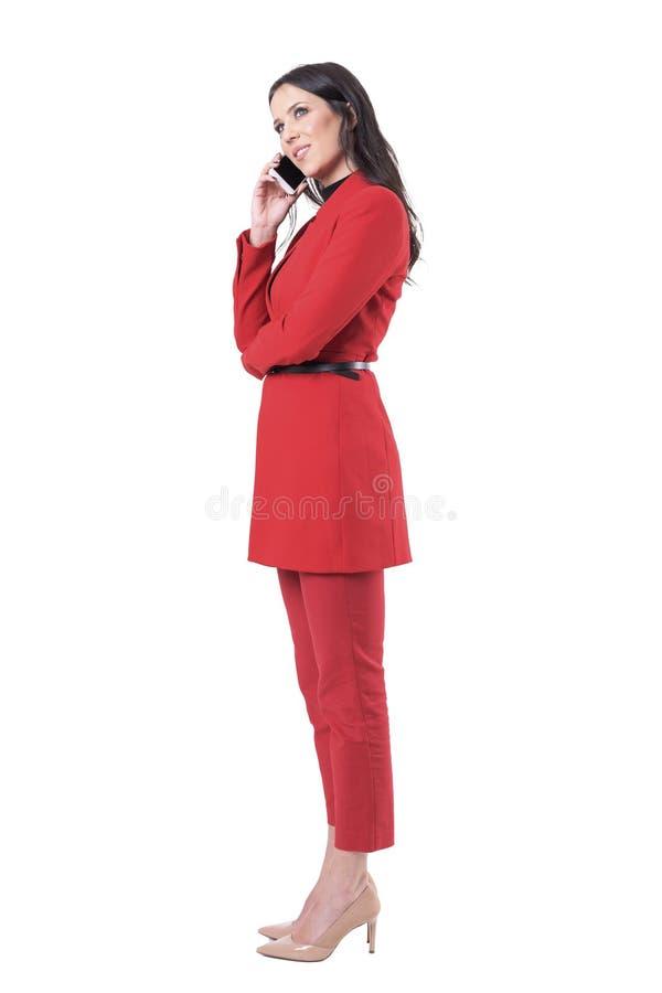 Vue de côté de la position attrayante décontractée heureuse et de parler de femme d'affaires sur le téléphone portable image libre de droits