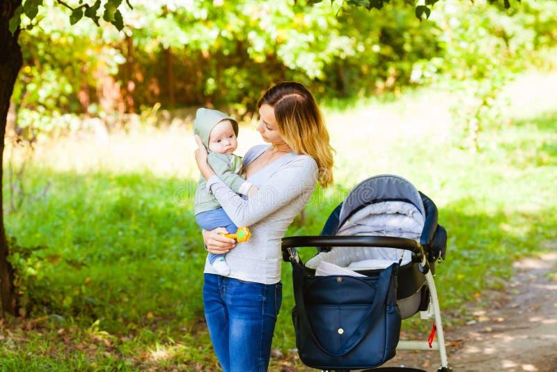 Vue de côté de la position de bébé de participation de mère près de la poussette photographie stock libre de droits