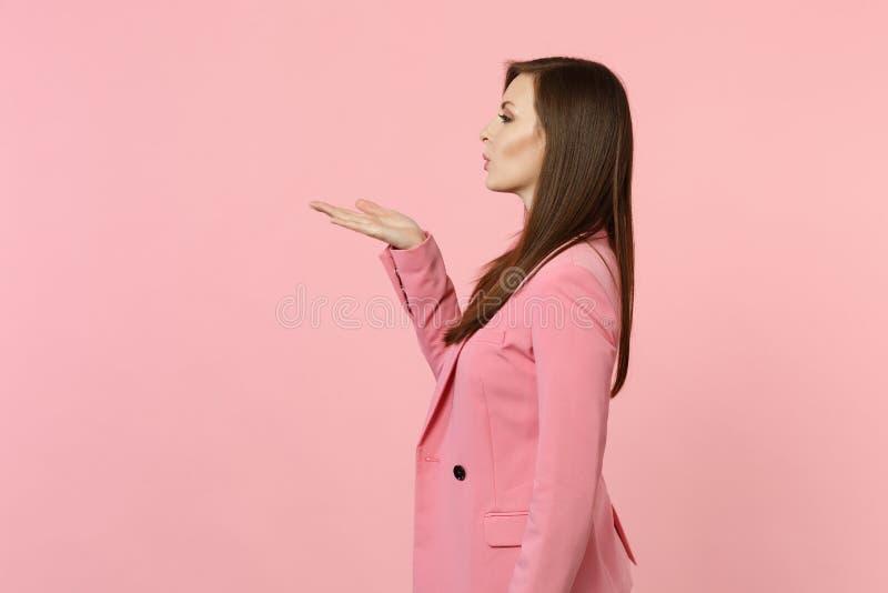 Vue de côté de la veste de port de belle jeune femme tendre soufflant envoyant le baiser d'air d'isolement sur le mur rose en pas photos stock