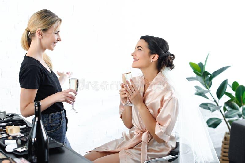 vue de côté de maquilleur et de jeune mariée de sourire dans le peignoir en soie avec des verres photographie stock