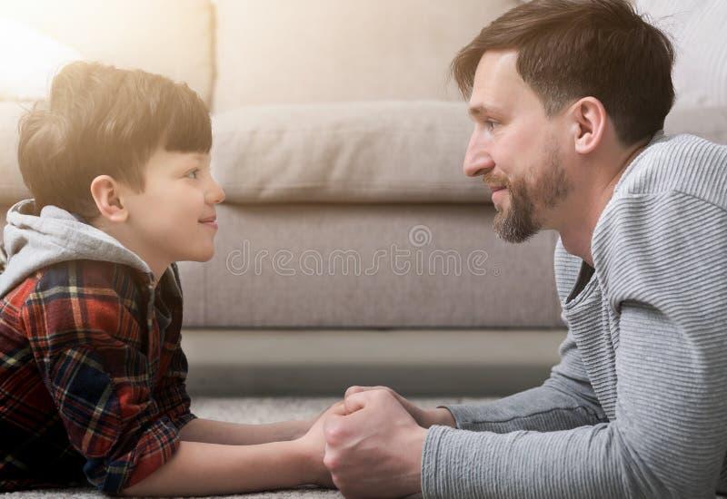 Vue de côté de père beau et de fils regardant l'un l'autre photo libre de droits