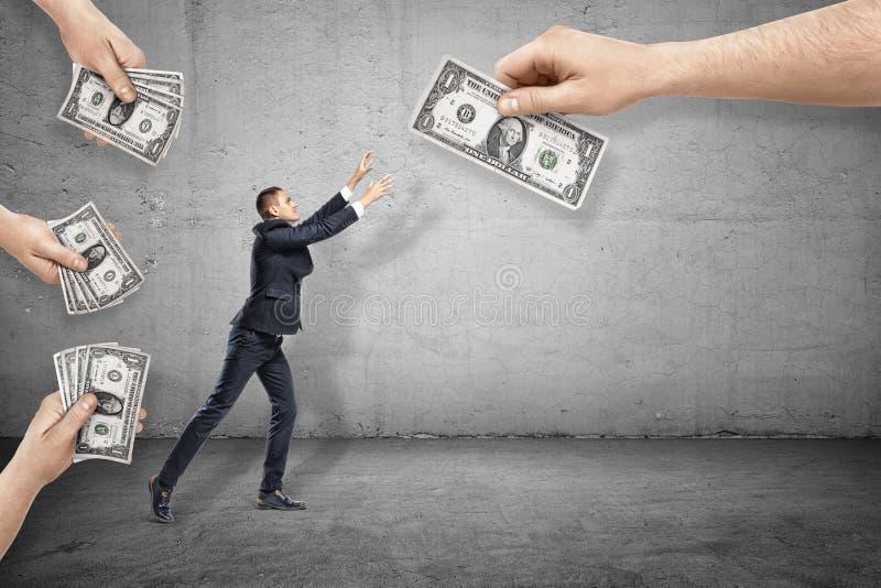 Vue de côté de peu d'homme d'affaires atteignant pour un de billets d'un dollar donnés à lui par de grandes mains tout autour images libres de droits
