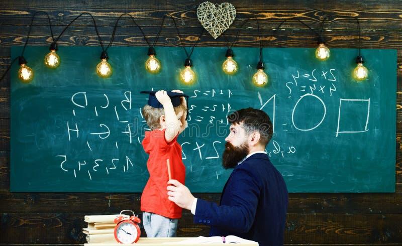 Vue de côté de professeur et de petit enfant devant le conseil vert Garçon enlevant le chapeau d'obtention du diplôme Type s'asse image libre de droits
