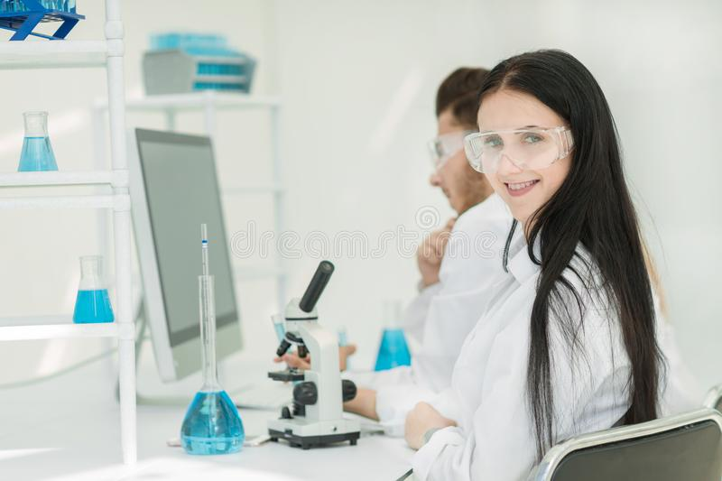 Vue de côté scientifique féminin s'asseyant à une table de laboratoire images stock