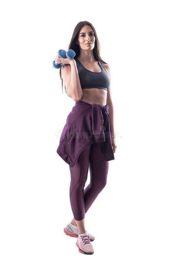 Vue de côté sportive active d'ajustement de jeune dans l'habillement de sports posant et tenant des haltères image stock