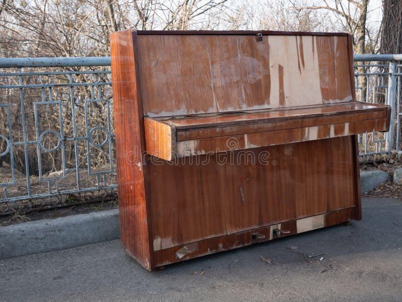 Vue de c?t? sur le r?tro piano en bois classique abandonn? au parc de ville concept de concert d'air ouvert photographie stock libre de droits