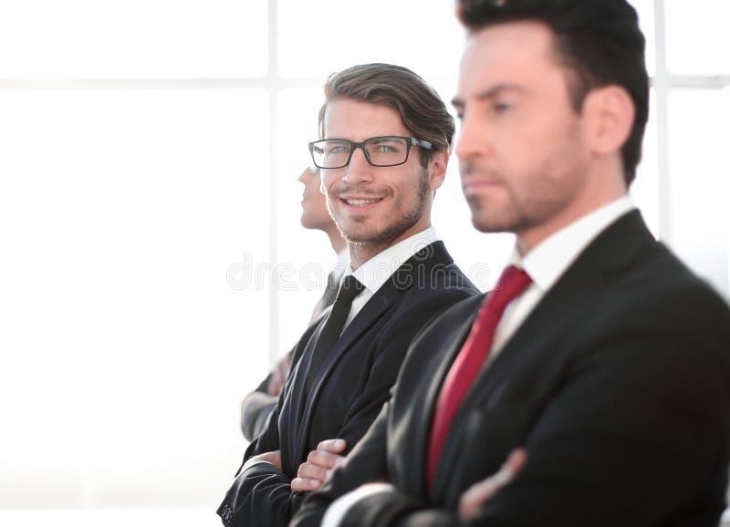 Vue de côté un groupe d'hommes d'affaires réfléchis se tenant près d'une fenêtre de bureau photos stock