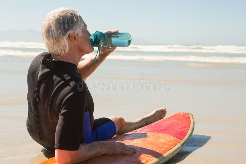 Vue de côté d'eau potable d'homme supérieur tout en se reposant sur la planche de surf image libre de droits