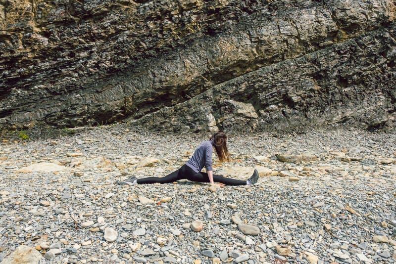 Vue de côté d'un chiffre mûr sain de femme s'étendant et s'exerçant sur une plate-forme de roche photo libre de droits