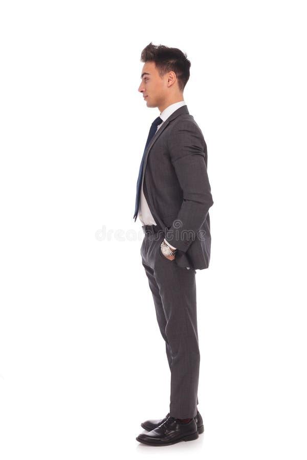 Vue de côté d'un jeune homme d'affaires se tenant dans la ligne images libres de droits