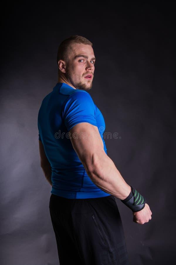 Vue de côté d'un jeune homme musculaire se tenant dans le studio, vue arrière sur le fond noir de studio photos stock