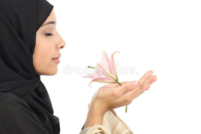 Vue de côté d'une femme arabe portant un hijab sentant une fleur image stock