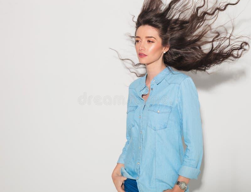 Vue de côté d'une jeune femme attirante avec les cheveux de flottement photos libres de droits