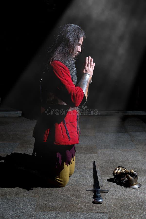 Vue de côté de chevalier Kneeling sur ses genoux et prière photos stock