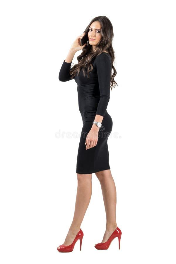 Vue de côté de femme élégante de marche d'affaires au téléphone image libre de droits