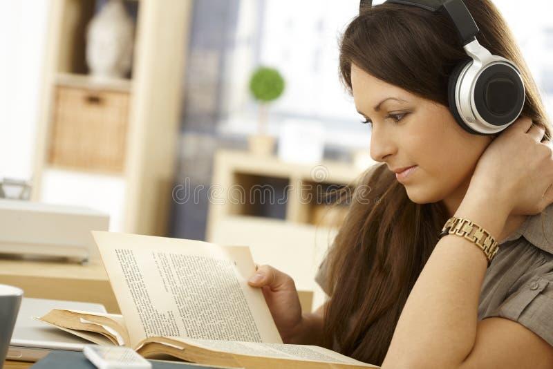 Vue de côté de femme de lecture avec des écouteurs photos libres de droits