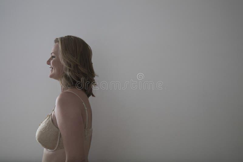Vue de côté de femme de sourire dans le soutien-gorge photographie stock