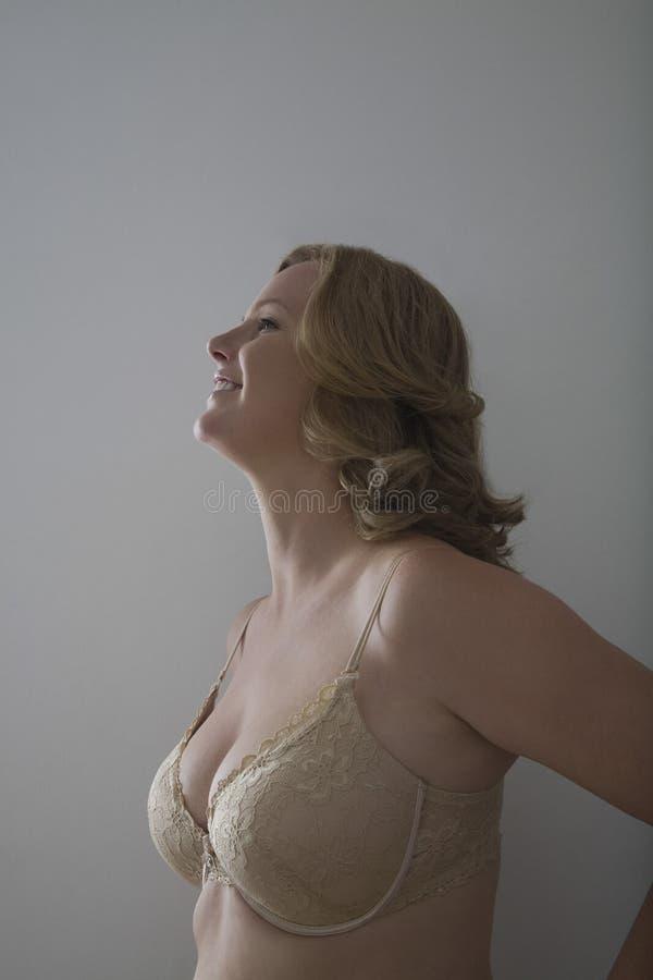 Vue de côté de femme de sourire dans le soutien-gorge images libres de droits