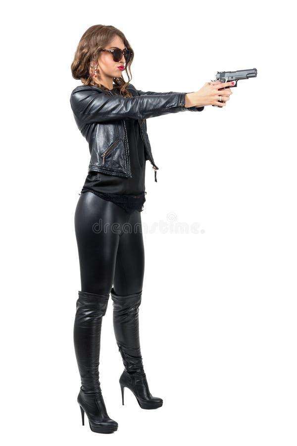 Vue de côté de femme dure dangereuse dans des vêtements en cuir tirant une arme à feu photos libres de droits
