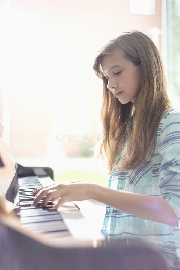 Vue de côté de fille jouant le piano à la maison image stock
