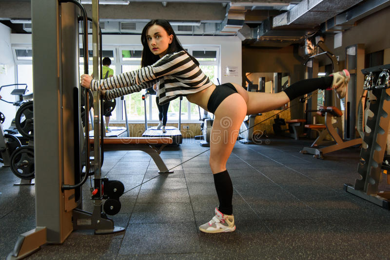 Vue de côté de fille sexy de forme physique de brune dans l'usage blanc et noir de sport avec le corps parfait posant au gymnase photo stock